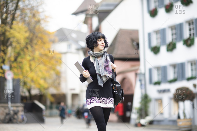 young woman walking outside with handbag and book