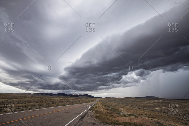 A thunderstorm approaches a rural road in the Montana plains