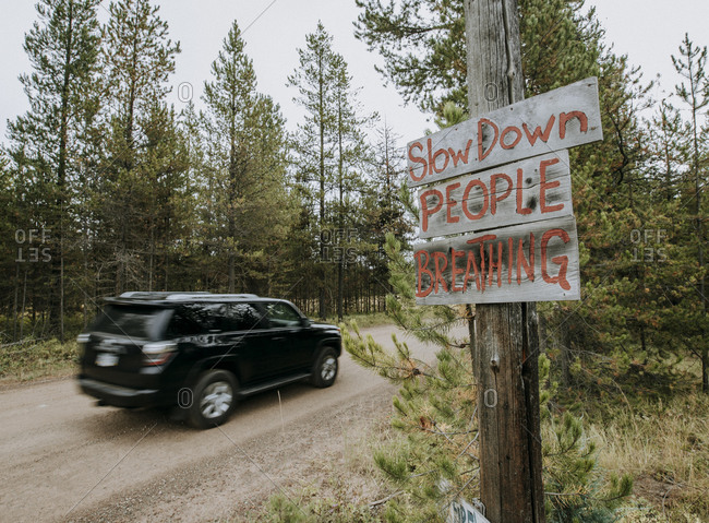 a sign on a dirt road with speeding car warning drivers to slow down
