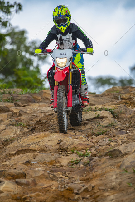 Woman on off road bike riding down a rough trail