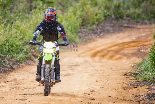 Woman on off road bike riding down a dirt road