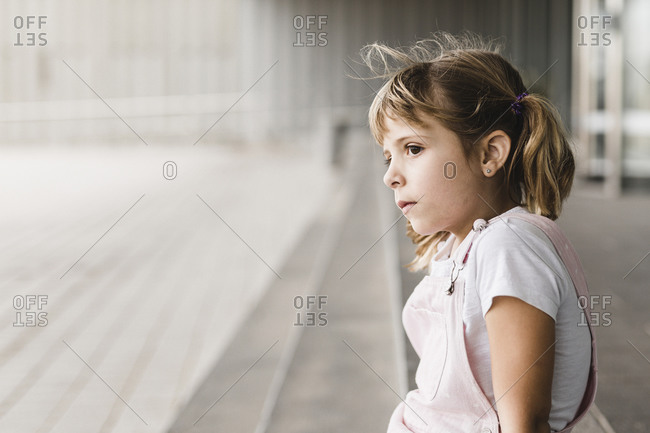 portrait of a blonde girl sitting and looking thoughtfully
