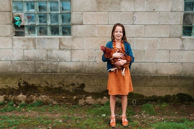 Smiling girl standing on a farm holding a chicken, USA