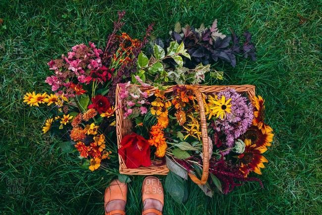 Overhead view of a girl standing by a basket filled with freshly picked flowers, USA