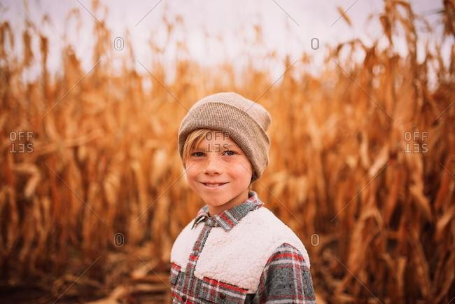 Smiling boy standing in a corn field in the fall, USA