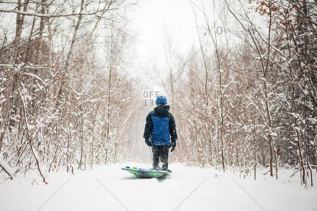 Boy pulling a sledge through the snow, Wisconsin, USA
