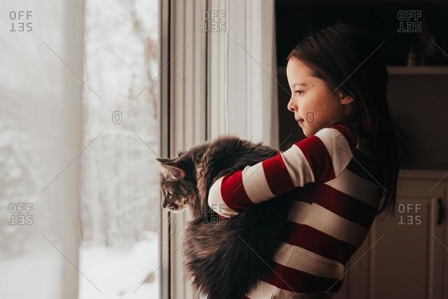 Girl standing by a window cuddling her cat