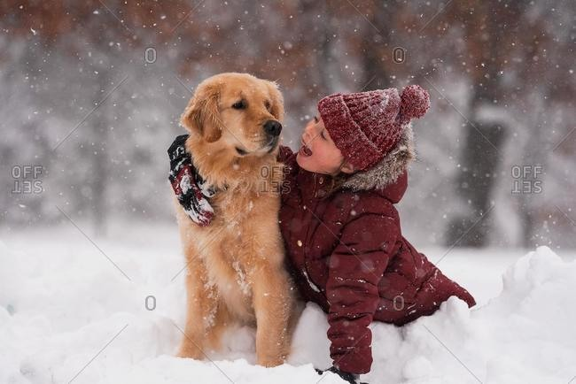Girl sitting in the snow cuddling her golden retriever dog, Wisconsin, USA