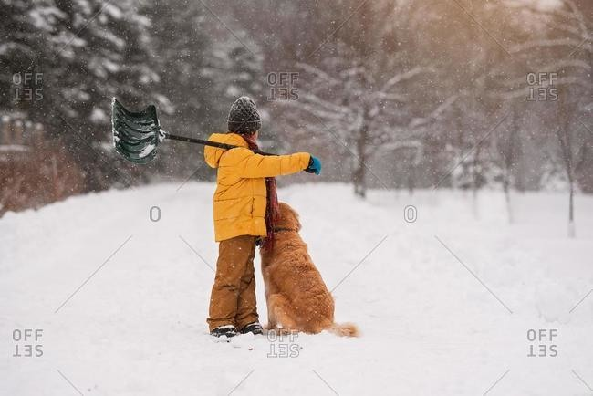 Boy with a shovel standing with his dog in the snow on a long snow covered driveway, Wisconsin, USA
