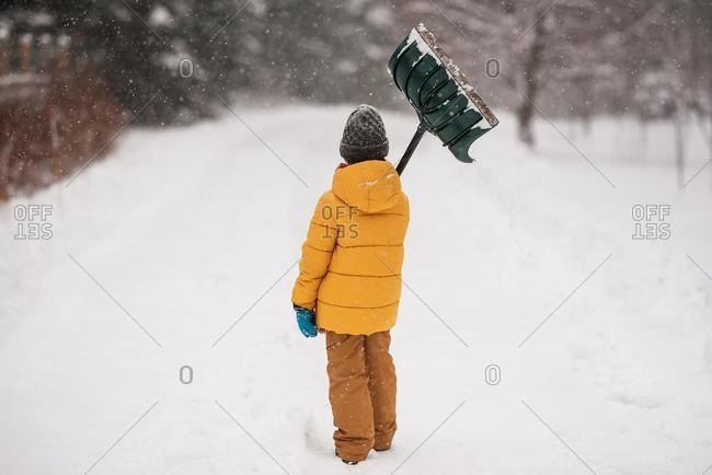 Boy with a shovel standing in the snow on a long snow covered driveway, Wisconsin, USA