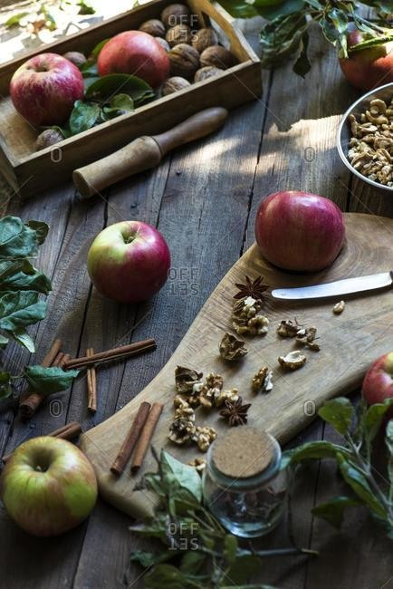 Apples, walnuts and spice arrangement on a wooden table