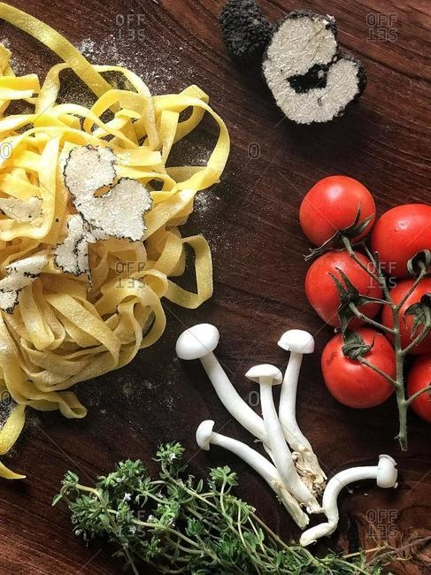 Fresh tagliatelle pasta with truffle shavings, mushroom, tomato and thyme