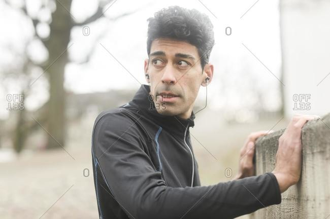Portrait of a male jogger warming up outside, Germany