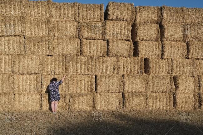Woman standing in front of a stack of hay bales in a field, France