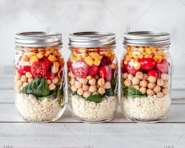 Three meal jars with millet, spinach, chickpea, tomato and corn