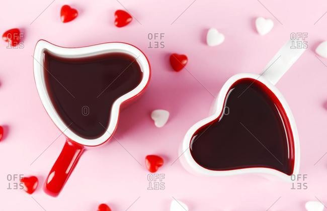 Two heart shape mugs and candy on pink background