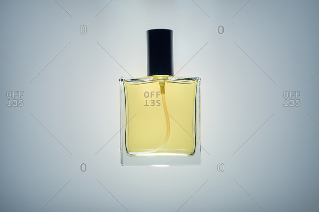 Transparent glass bottle of luxury perfume with fancy scent isolated on gray background