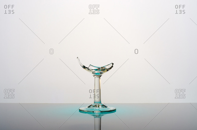 Damaged glass goblet with sharp edges placed on table against gray background
