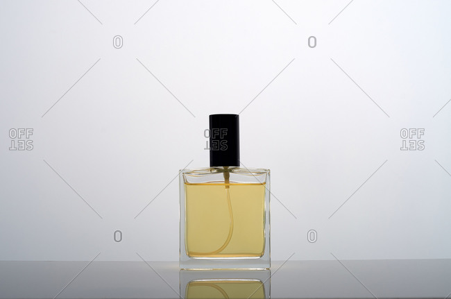 Glass bottle with golden perfume placed on reflective table against gray background