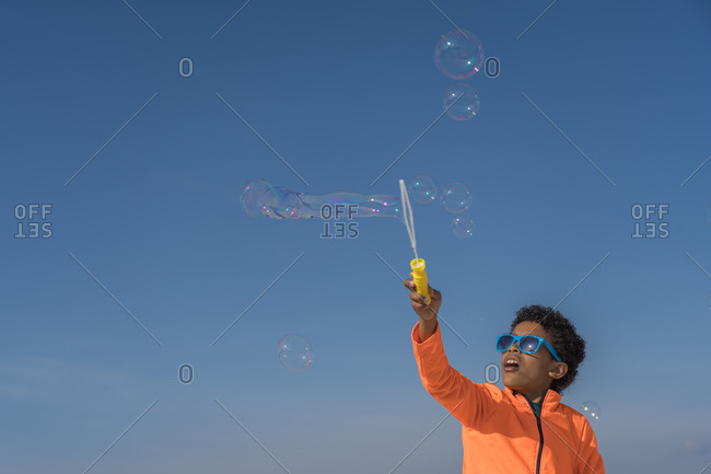Black boy playing with soap bubbles in the park