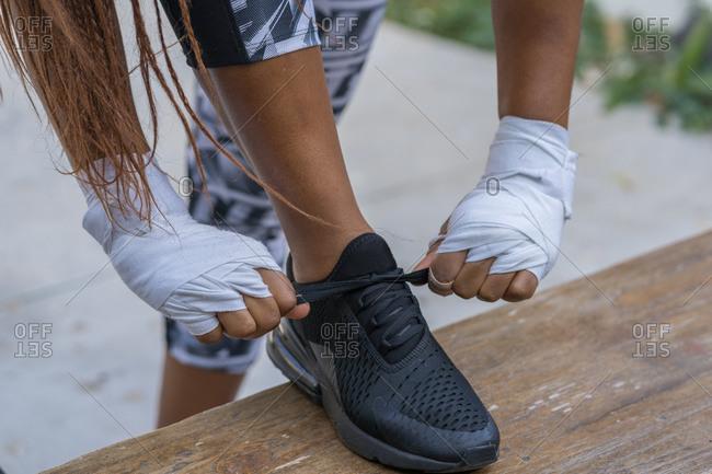 Closeup of female cuban boxer feet tying shoes before training