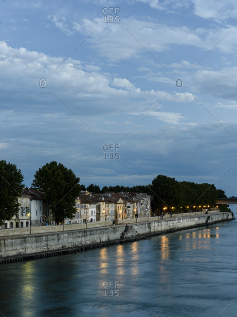 The Rhone river and embankment at dusk in Arles, Camargue, Bouches-du-Rhone, France
