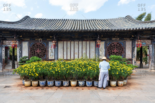 Jianshui, China - March 7, 2019: March 7, 2019: Gardener taking care of some plants in a historic building at the city of Jianshui, Yunnan, China