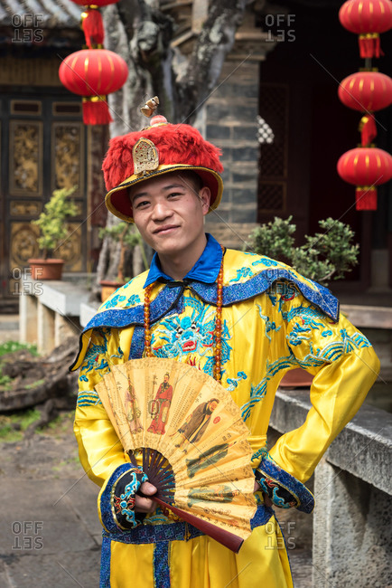 Jianshui, China - March 7, 2019: March 7, 2019: A Chinese man dressed with traditional old clothes in front of an historic house in Jianshui, China