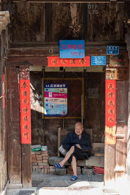 Jianshui, China - March 7, 2019: March 7, 2019: Chinese elder man on a chair, Jianshui, Yunnan, China