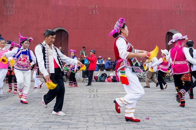 Jianshui, China - March 8, 2019: March 8, 2019: People gathering and dancing with traditional dresses in front of the famous Chaoyang Gate in Jianshui, Yunnan, China