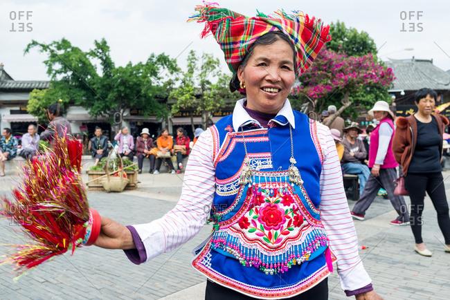Jianshui, China - March 8, 2019: March 8, 2019: Senior Chinese woman dancing with traditional dress in front of the famous Chaoyang Gate in Jianshui, Yunnan, China