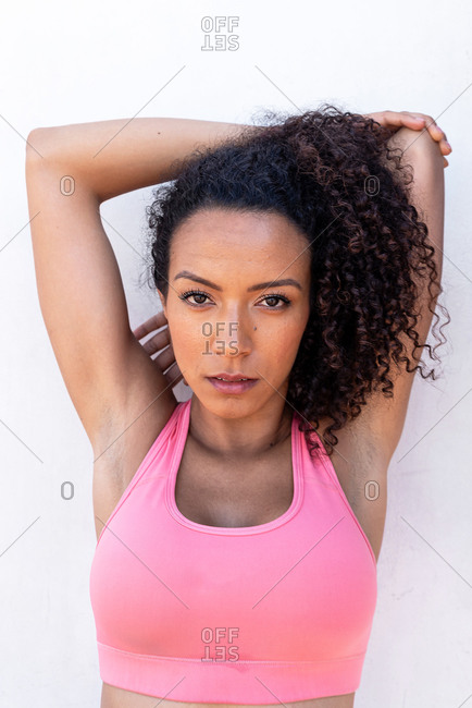 Portrait of a Latin American woman jogger with a pink top stretching outdoors on a white background