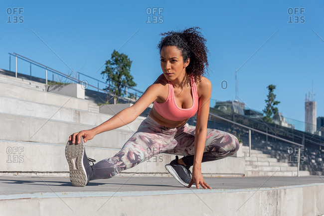 Latin American woman jogger stretching outdoors in a urban park
