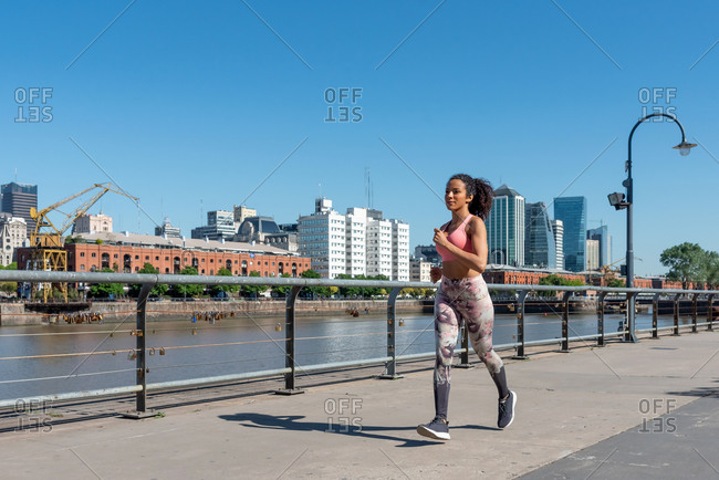Latin American woman with a pink outfit jogging in Puerto Madero, Buenos Aires