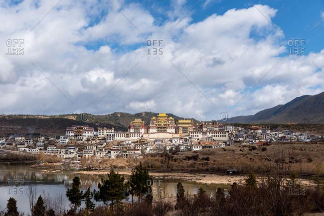 Songzanlin Tibetan Buddhist Monastery reflected in sacred lake. Shangri-La, Yunnan Province, China