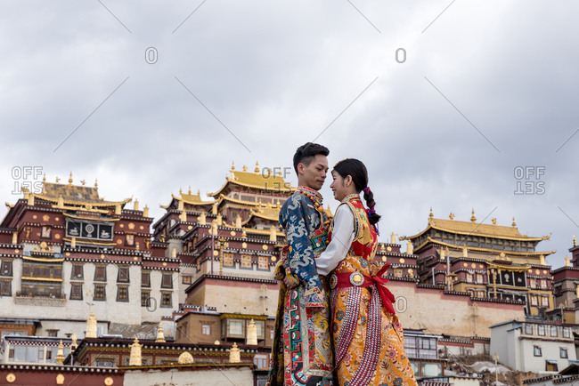 Shangri-la, China - March 20, 2019: March, 20. 2019: Couple with traditional costumes in front of Songzanlin Tibetan Buddhist Monastery. Shangri-La, Yunnan Province, China