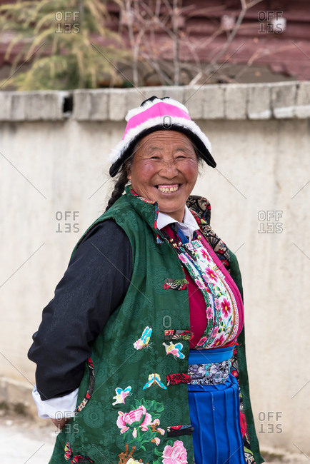 Shangri-la, China - March 20, 2019: March 20, 2019: Tibetan woman walking in front of the Songzanlin monastery. Shangri-la, Yunnan, China
