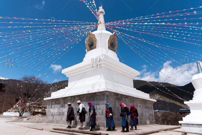 Shangri-la, China - March 21, 2019: March 21, 2019: Praying at a buddhist Stupa With Tibetan Flags In Himalayan Mountains. Shangri-la, Yunnan, China