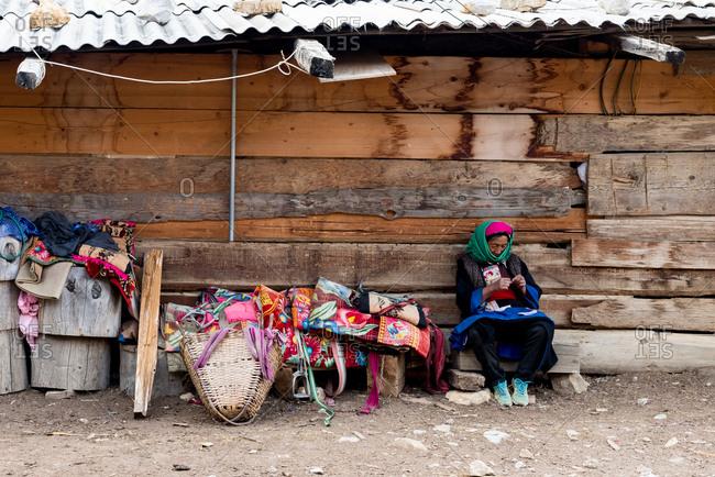 Shangri-la, China - March 21, 2019: March 21, 2019: Tibetan woman and her small stall. Shangri La, Yunnan, China