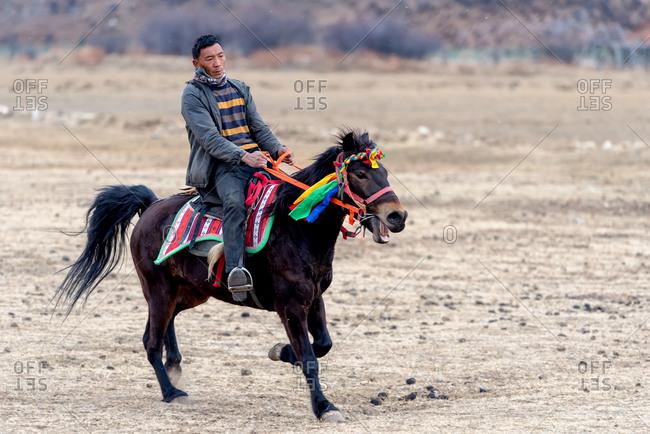 Shangri-la, China - March 21, 2019: March 21, 2019: Man riding a horse. Shangri-la, Yunnan, China