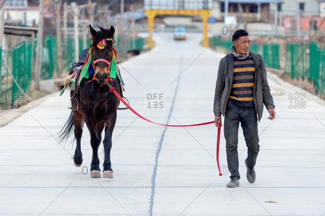 Shangri-la, China - March 21, 2019: March 21, 2019: Man walking with his horse. Shangri-la, Yunnan, China