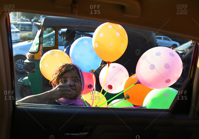 Jaipur, India - January 3, 2020: Homeless girl begging for food and money selling balloons on street to man inside car at red light