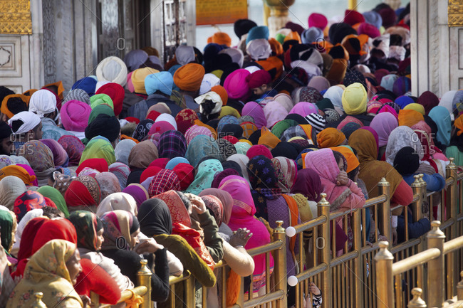 Amritsar, India - January 6, 2020: Sikh worshippers with colorful head covers at the Golden Temple entrance