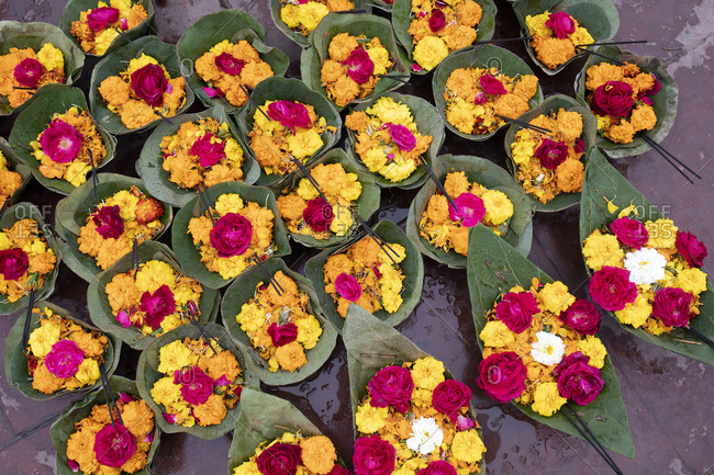 Flowers in floating bowls for sale to Hindu religious tourists to put into the Ganges River for blessings