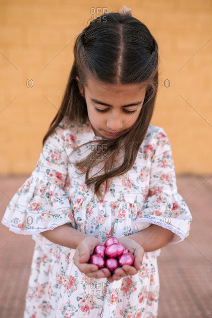 Little girl in dress holding pink candy, Easter eggs