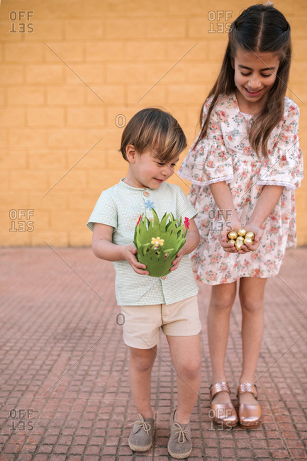 Brother and sister with Easter egg basket in the street