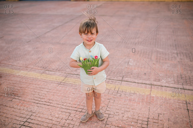 Portrait of three year old blond boy with green basket in the street