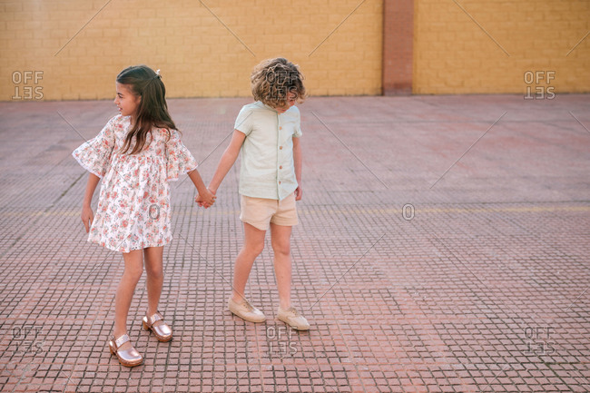 Two Caucasian siblings holding hands in the street