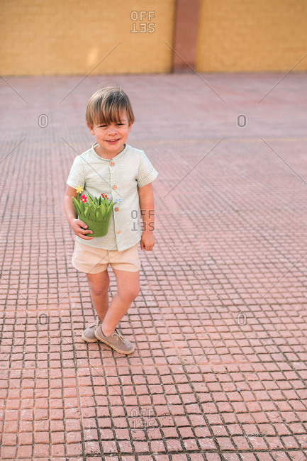 Portrait of young blond boy with green basket in the street