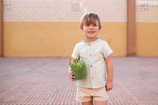 Portrait of blond preschooler boy with green basket in the street